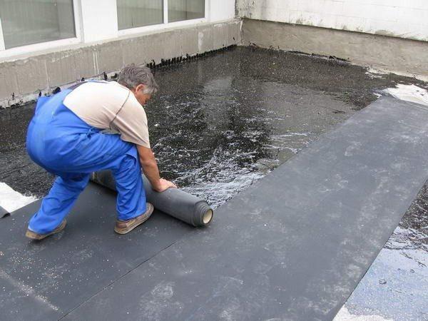 Процесс укладки рубероида на бетонную крышу
