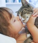 ребёнок целует кошку