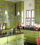 Светло-зелёная мебель и красные детали на кухне
