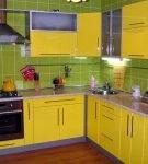 Зелёный фартук и жёлтые фасады мебели на кухне