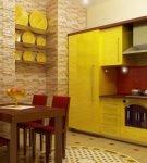 Жёлтая мебель и красный фартук на кухне