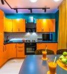 Оранжевый гарнитур на фоне синей стены кухни