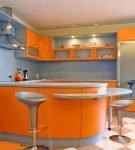 Оранжевая мебель и стены пыльно-голубого цвета на кухне