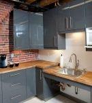 Кирпичная стена в сочетании с серым гарнитуром на кухне