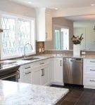 Светло-серая столешница в просторной кухне
