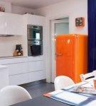 Оранжевый холодильник на светлом фоне кухни ретро