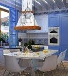 Синие детали и круглый обеденный стол на кухне