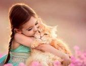 Девочка в зелёном платье обнимает рыжего кота