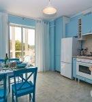 Голубая мебель и стены на просторной кухне