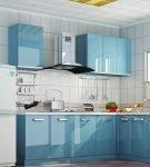 Голубая мебель на фоне белых стен кухни