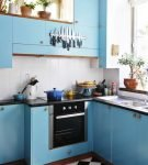 Чёрно-белый пол и голубая мебель на кухне