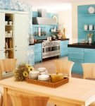 Голубой гарнитур и бежевый стол на кухне