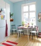 Белая мебель на кухне с голубой стеной