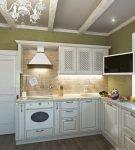 Белая мебель на фоне зелёных стен кухни прованс
