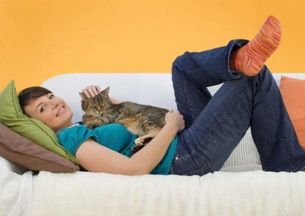 Девушка и кот лежат на диване