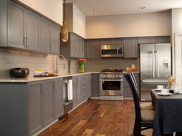 Серая мебель на кухне с коричневым напольным покрытием