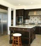 Островной стол на кухне с тёмно-коричневой мебелью