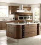 Остров на кухне с коричневой стильной мебелью