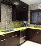 Зелёная столешница и коричневая мебель на кухне