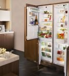 Широкий холодильник за дверьми шкафа