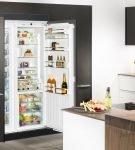 Холодильник, встроенный в большой тёмный шкаф