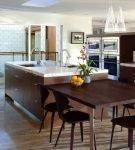Обеденный стол на кухне с островом коричневого цвета