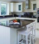Белый стол с тёмной столешницей на кухне