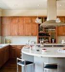 Белый остров и коричневая мебель на кухне