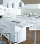 Белая мебель на кухне с коричневым напольным покрытием
