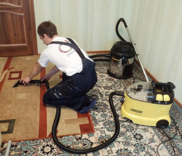 Мужчина чистит ковёр