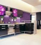 Большая кухня с чёрно-фиолетовым гарнитуром и яркой стеной