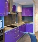 Фиолетовая мебель с белой столешницей на маленькой кухне