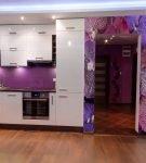 Сочетание фиолетового фартука, белой мебели и ярких обоев на кухне