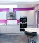Белая мебель на фоне фиолетовой стены кухни