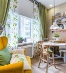 Яркая мебель и зелёные шторы на кухне с жидкими обоями