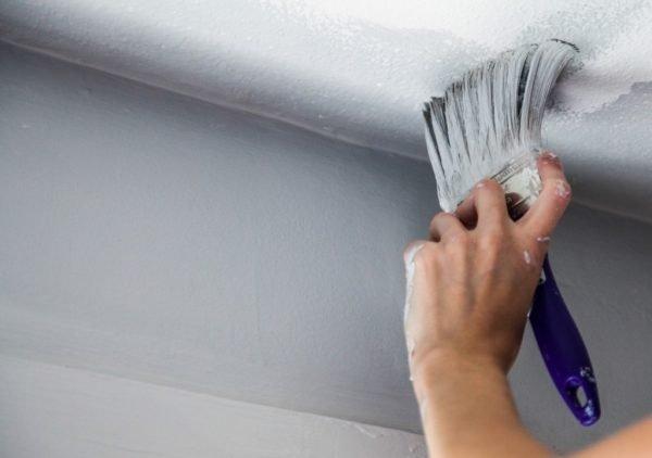 Процесс нанесения краски по периметру потолка