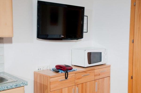 Телевизор над микроволновкой, подвешенный на кронштейн