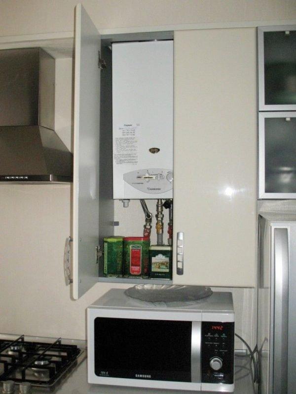 Газовая колонка с трубами в кухонном шкафчике