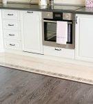 Сочетание тёмного ламината и белой плитки на кухне