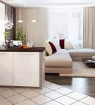 Белая плитка на кухне и тёмный ламинат в зоне гостиной