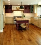 Кухня со светлой мебелью и коричневым ламинатом
