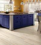 Сине-белая мебель на кухне со светлым ламинатом