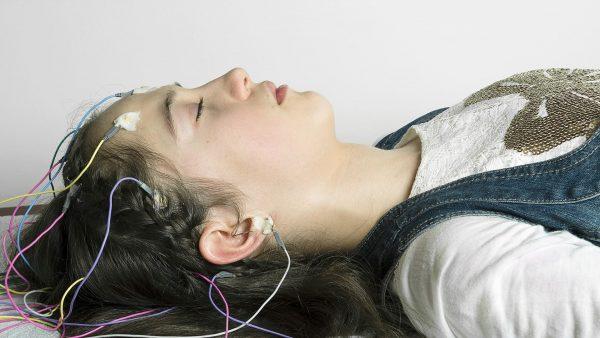Девушка спит с датчиками ЭЭГ, отслеживающими работу головного мозга