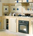 Кухня, стены и пол которой отделаны бежевой и белой плиткой
