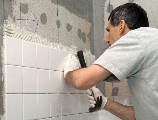 Процесс приклеивания плитки к стене