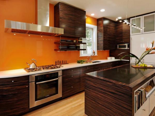 Коричневая мебель и оранжевая стена на кухне