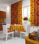 Пёстрые оранжевые шторы на кухне со светлой мебелью