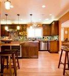 Просторная кухня с барной стойкой и оранжевыми стенами
