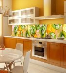 Яркий фартук на кухне с гарнитуром терракотового цвета