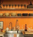 Оранжевая стена с полками на кухне